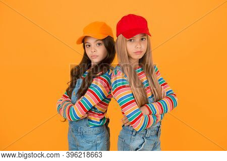 Fashion That Matches Their Conscious Style. Small Girls In Style Keeping Arms Crossed On Yellow Back