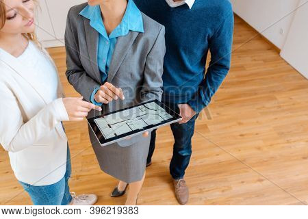 Accommodation broker showing floor plan of apartment to clients wanting to buy or rent