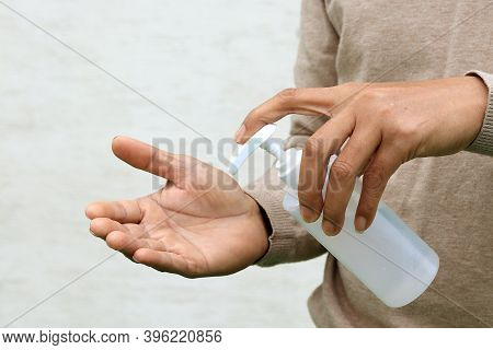 Man Using Hand Press Bottle And Pouring Alcohol-based Sanitizer On Other Hands,   To Prevent The Vir