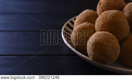 Arancini, Italian Street Food. Fried Balls, Made Of Rice, Meat And Vegetables On A Plate And A Blue