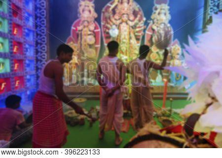 Blured Image Of Kansor Ghonta, Played By Hindu Devotee While Bengali Priest Worships Goddess Durga,
