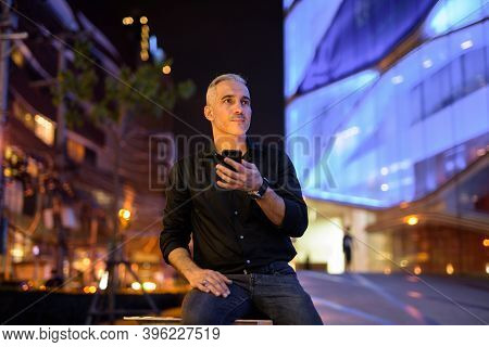 Handsome Man At Night On The Streets Using Mobile Phone While Thinking