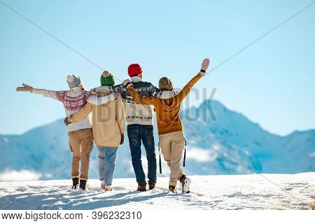 Four Happy Friends Are Standing And Embracing Against Snow Capped Mountains At Sunny Day. Winter Vac