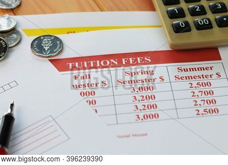 Close Up Paper Of School Tuition Fees On Wooden Table With Coins, Red Pen, And Calculator