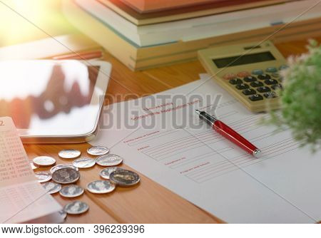 School Scholarship Application Form On Wooden Table With Books, Coins, Calculator And Ipad