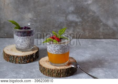 Dessert With Chia Seeds And Berries In Glass Glasses On Wooden Cuts On A Gray Background. Superfoods