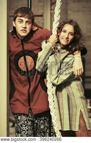 Happy young fashion hipster couple on the playground  Stylish trendy man and woman in hooded sweatshirt