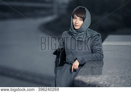 Young fashion woman with handbag leaning on parapet Stylish female model in gray classic coat and head scarf
