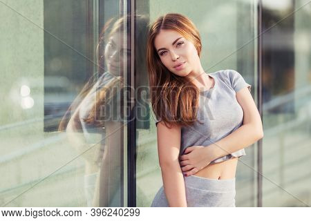 Happy young fashion woman leaning on mall window Stylish female model  in gray crop top and skirt suit
