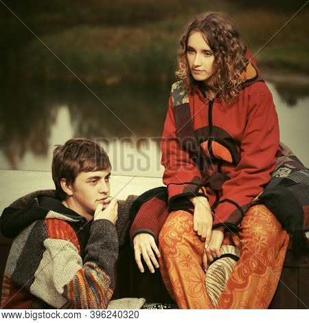 Young fashion hipster couple sitting on parapet  Stylish trendy man and woman in hoodie sweatshirt