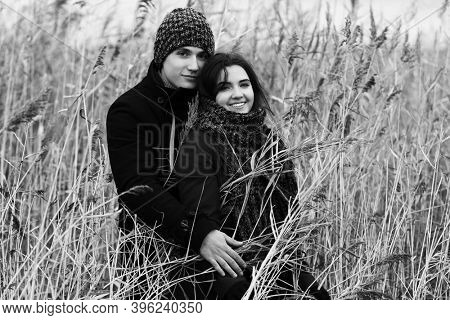 Happy young fashion couple walking in thickets of bulrush Stylish man and woman in classic coats beanie and scarf