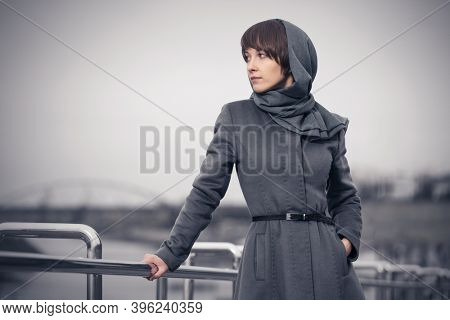 Young fashion woman leaning on railing Stylish female model in gray classic coat and head scarf