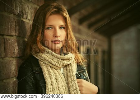 Young fashion girl in leather jacket and knitted scarf leaning on brick wall