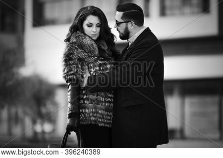 Young fashion couple in conflict on city street Stylish trendy man in classic black coat and woman in fox fur jacket