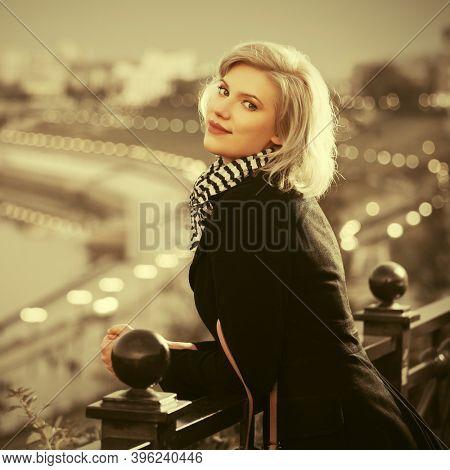 Fashion blonde woman leaning on railing  Stylish female model in black coat and white scarf