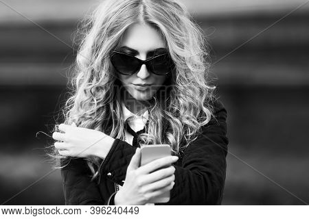 Blonde business woman using cell phone on city street Stylish fashion model with long curly hairs in black jacket and sunglasses