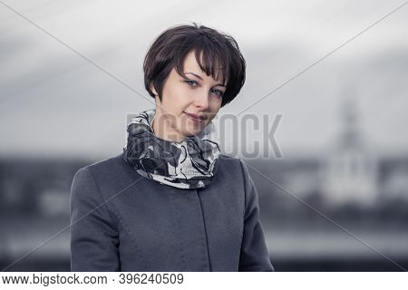 Young fashion woman with pixie hair style walking on city street Stylish female model in gray classic coat and scarf