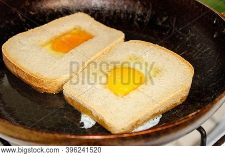 Eggs Are Fried In A Pan With Square Bread. Selective Focus.