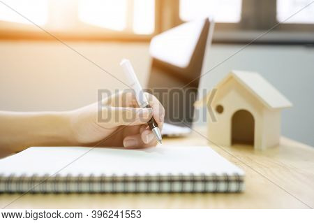 Close Up Hand Of Man Take Notes In A Notebook Plan To Be A Landlord. Mortgage And Real Estate Proper