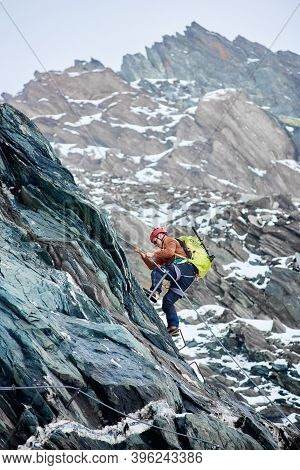 Side View Of Man Climber With Backpack Using Fixed Rope To Climb High Rocky Mountain, Ascending Alpi