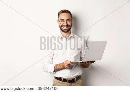 Business. Sucessful Businessman Working With Laptop, Using Computer And Smiling, Standing Over White