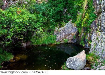 Waterfall In Manteigas Town, Serra Da Estrela Or Mountain Of Star In Portugal Called Poco Do Inferno