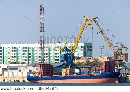 Industrial Landscape With Port Cranes In The Port On The Background Of The City View.