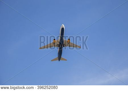 White Plane Flies In The Sky. Bottom View. Takeoff And Landing. Arrival And Departure. Passenger Pla