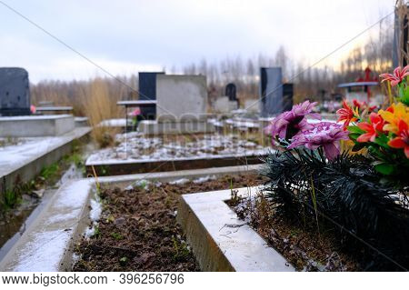 Flowers On The Grave And Bluring Cemetery At Background.
