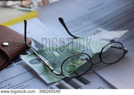 Brown Leather Wallet, 100 Euro Banknote, Glasses And Financial Report. Finance Profit And Loss Analy