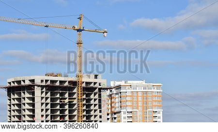 Construction Site At Rooftop Of Unfinished Skyscraper With Crane Jib Lifted Up Construction Material