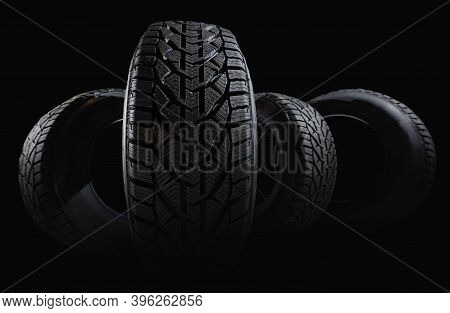 Stack Of Four New Black Tyres For Winter Car On Black Background