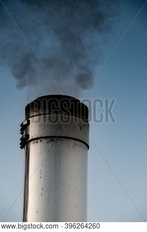 Smoking Stainless Steel Chimney In Front Of Morning Sky. High Quality Photo
