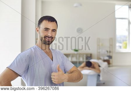 Smiling Man Doctor Chiropractor Or Masseur Showing Thumbs Up Sign