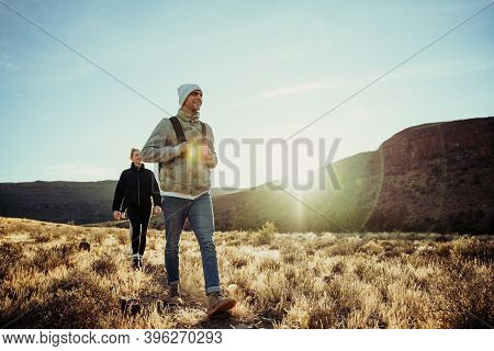 Young Teens Hiking In Luscious Mountain Terrain During Sunset