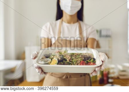 Responsible Takeaway Cafe Worker In Face Mask Holding Packed Lunch Ready For Delivery