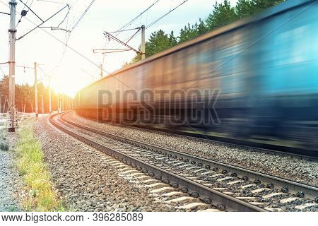 Motion Blurred Heavy Cargo Freight Rusty Train Wagons Moving On Railway On Sunset Or Sunrise Day Tim