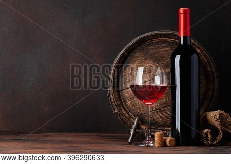 Wine bottle, glass of red wine and old wooden barrel. With copy space
