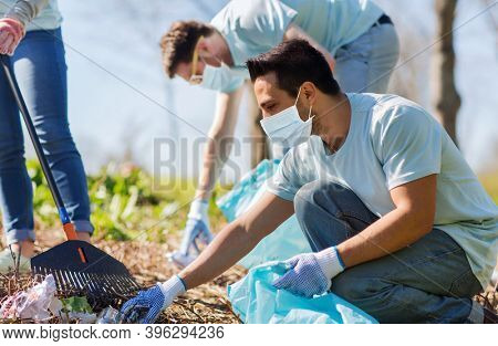 volunteering, charity, health and ecology concept - group of volunteers wearing face protective medical masks for protection from virus disease with garbage bags cleaning area in park