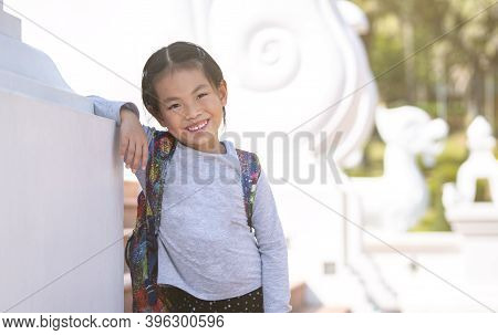 Portrait Asian Tourist Little Girl In The Temple Of Thailand, Carry A Backpack, Wears Long Sleeve Te