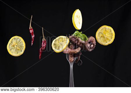 Octopus On A Fork With Lemon Slices, Green Basil Leaves And Red Hot Pepper .