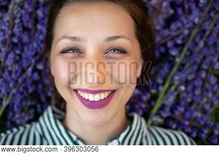 Close-up Portrait Of Beautiful Smiling Joyful Girl With Expressive Lilac Lips Looking At Camera On P