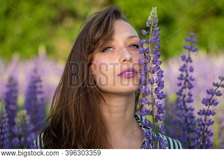 Gorgeous Beautiful Girl Leans Face Against Lupin Flower Sensually Looking At Camera On Blooming Mead