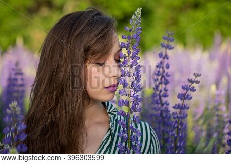 Gorgeous Beautiful Girl Eyes Closed Leans Head Against Lupin Flower On Blooming Meadow, Merging With