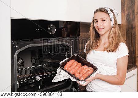 Girl Holding A Package With Sausages. Cooking Sausages In The Oven.