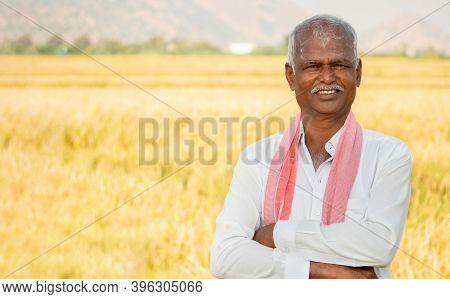 Portrait Of Confident Smiling Indian Farmer With Arms Crossed Standing In Front Of Agriculture Farml