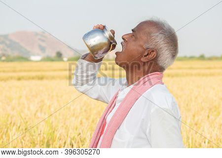 Thirsty Indian Farmer Drinking Water From Steel Tumbler Or Chambu On Hot Sunny Day At Agriculture Fi
