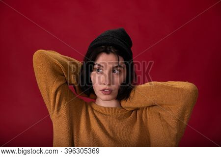 Brunette Hipster Girl In Black Knitted Cap And Mustard Sweater Posing With Hands Up On Red Studio Ba