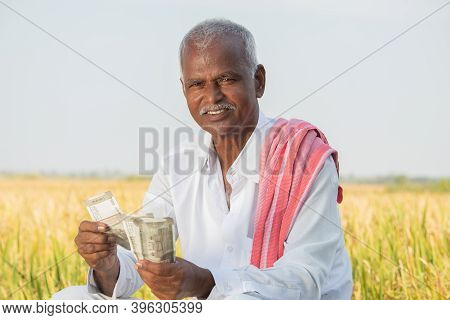 Happy Smiling Indian Farmer Counting Money On Agriculture Field While Looking Camera - Concept Of Go