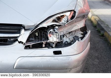 Car Crash Or Accident. Front Fender And Light Damage And Scratches On Bumper. Broken Vehicle Close U